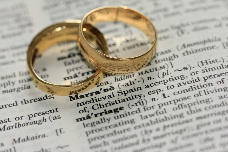 definition of marriage in dictionary with two wedding bands sitting on the page
