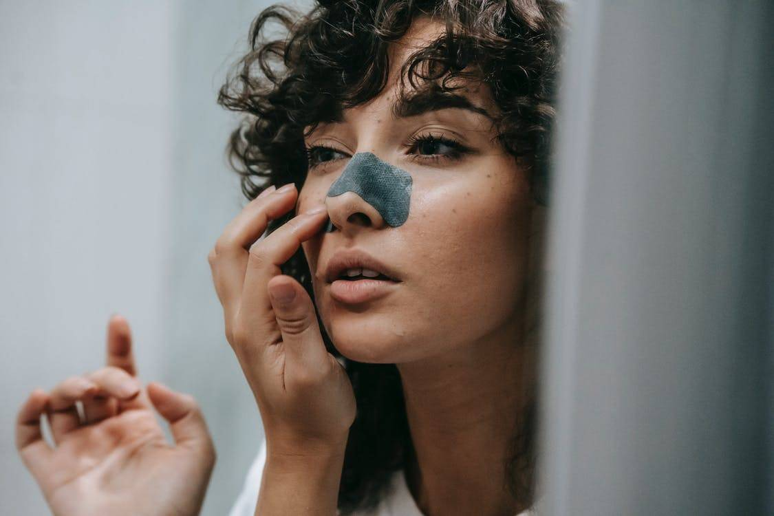 woman applying nose strip while looking in mirror