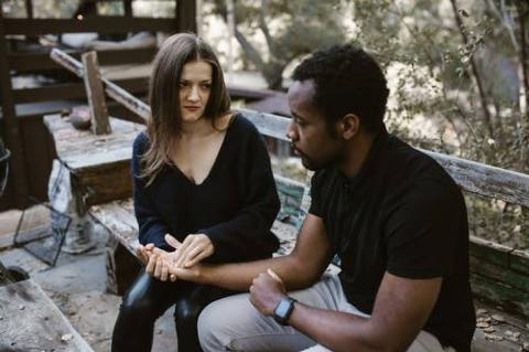 couple talking on a bench looking solemn