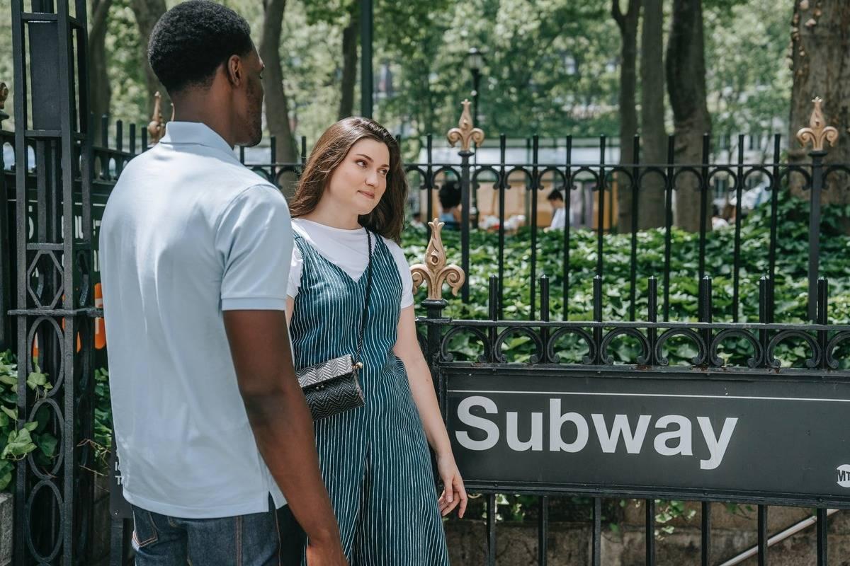 Woman looking away from man toward subway entrance