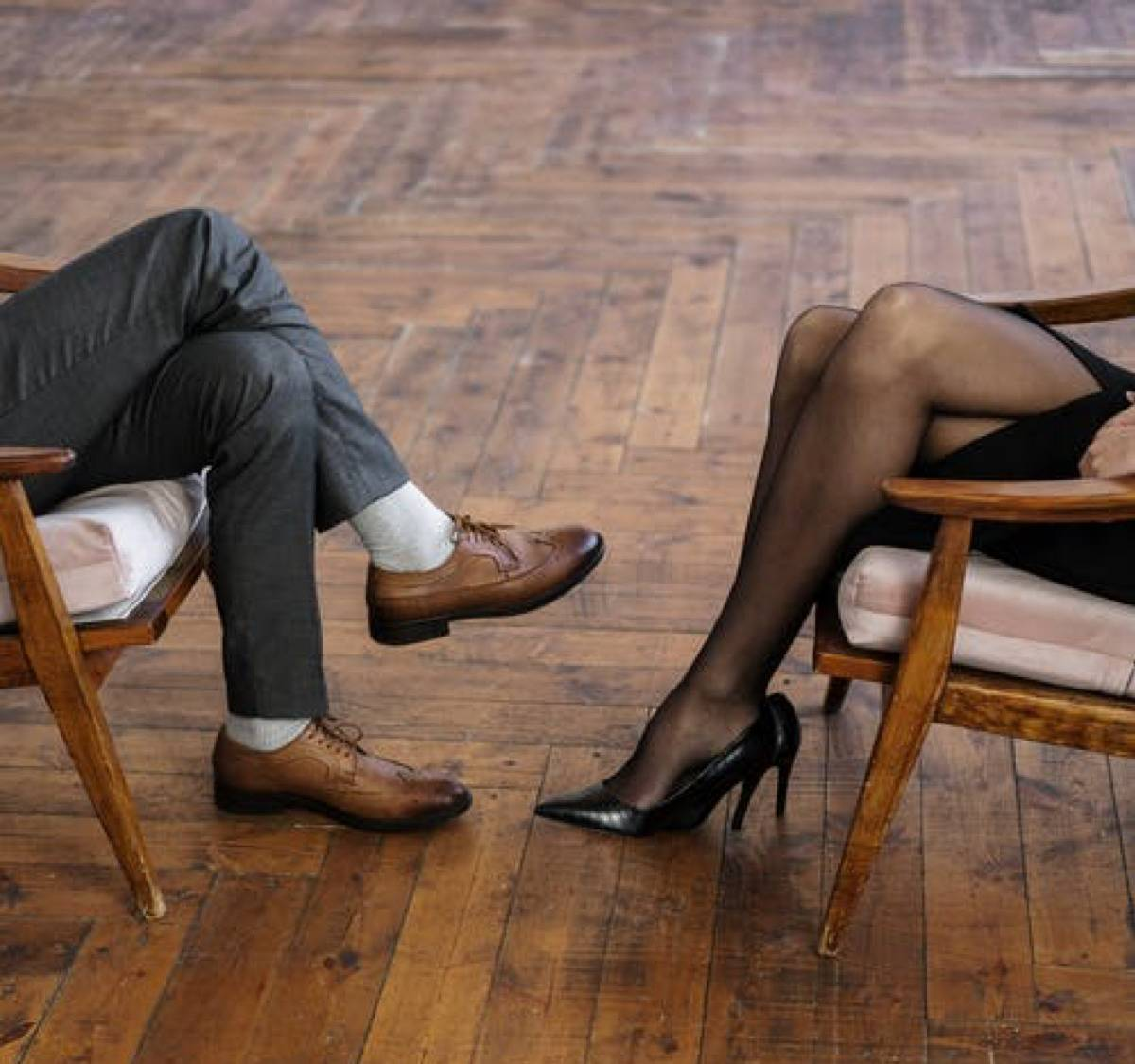 man and woman's feet seen as they sit in chairs facing each other