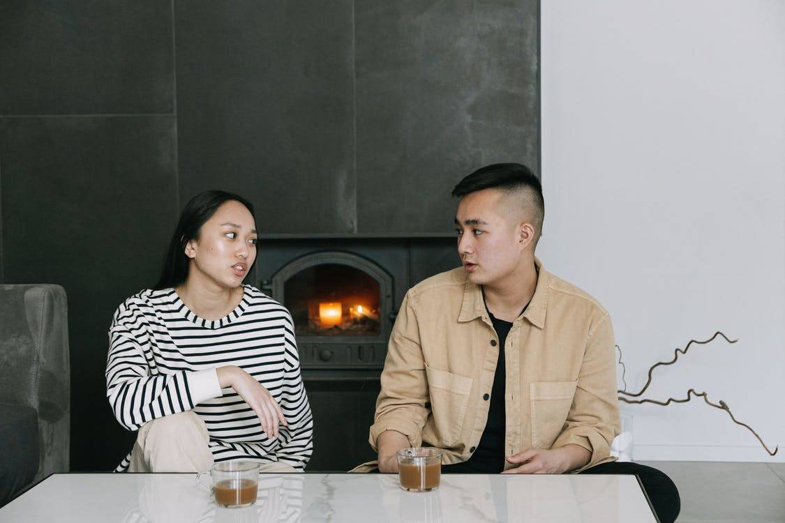 two people talking at home with drinks