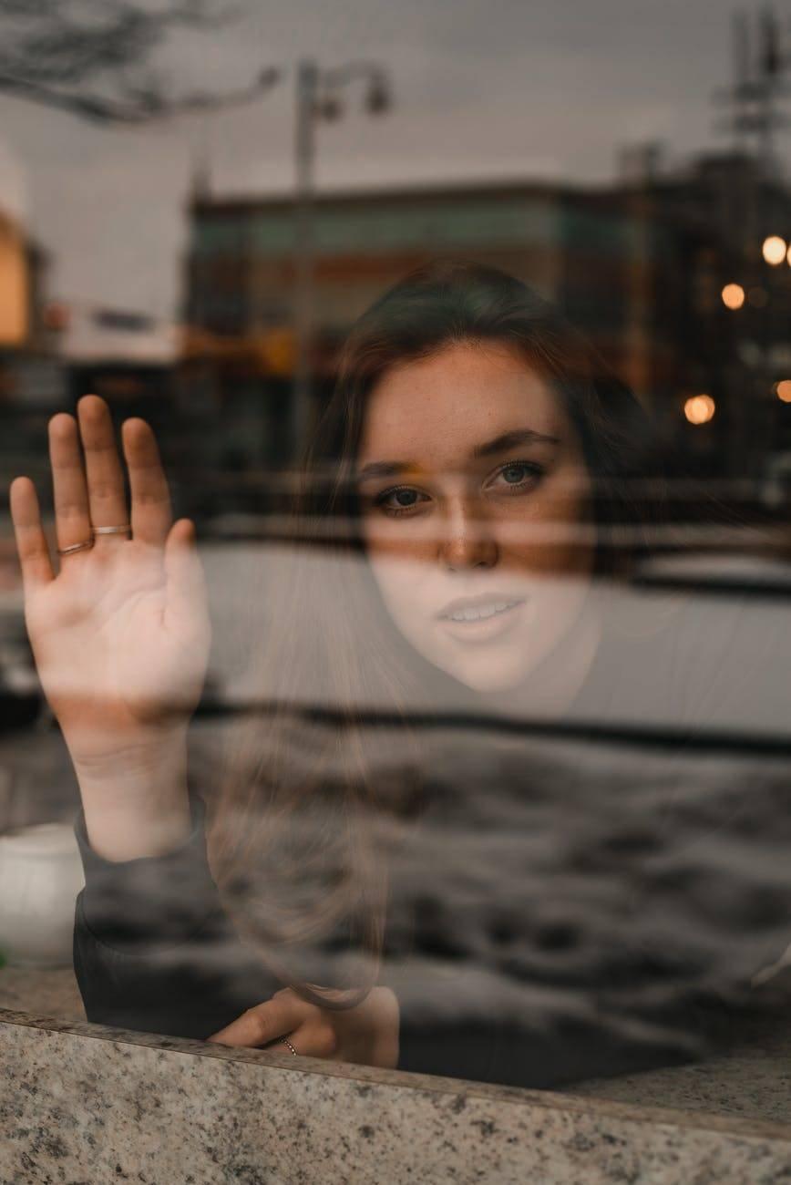 woman waving from inside window