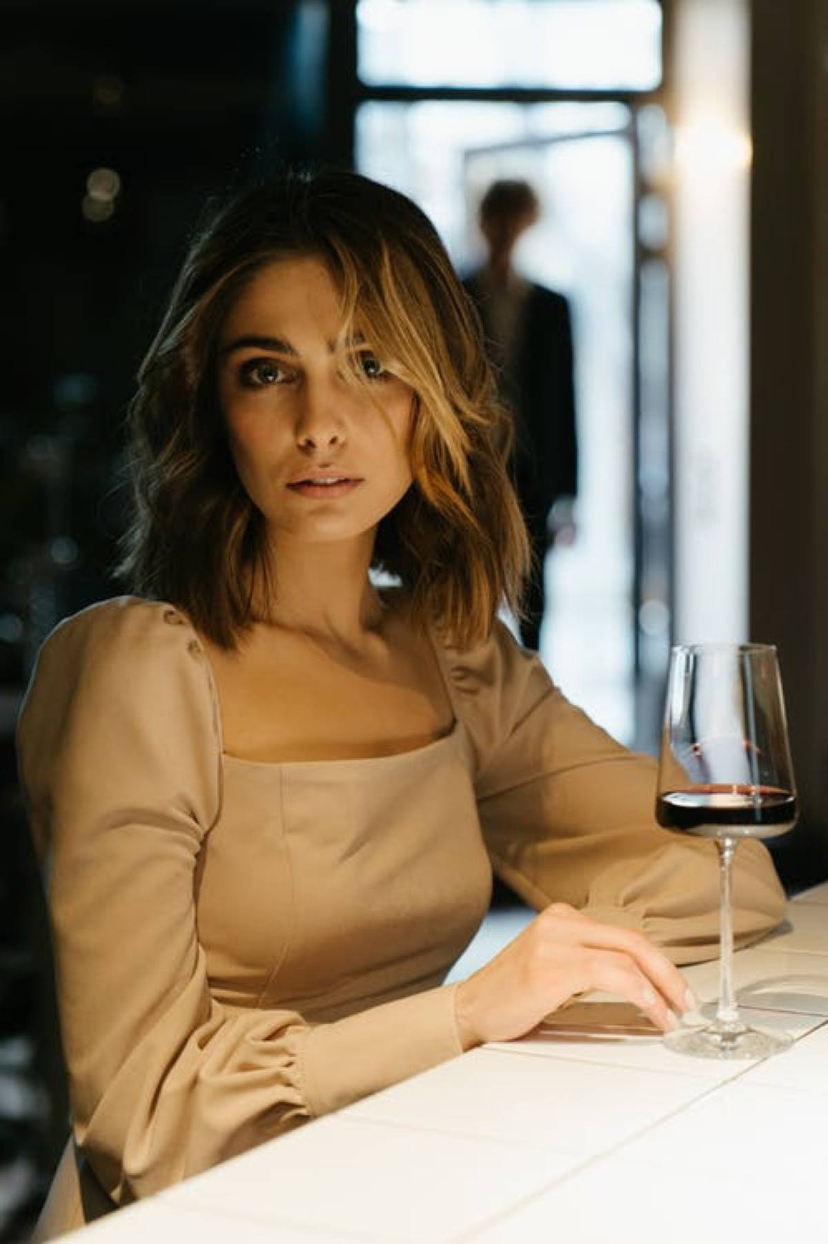 woman sitting with glass of red wine at bar