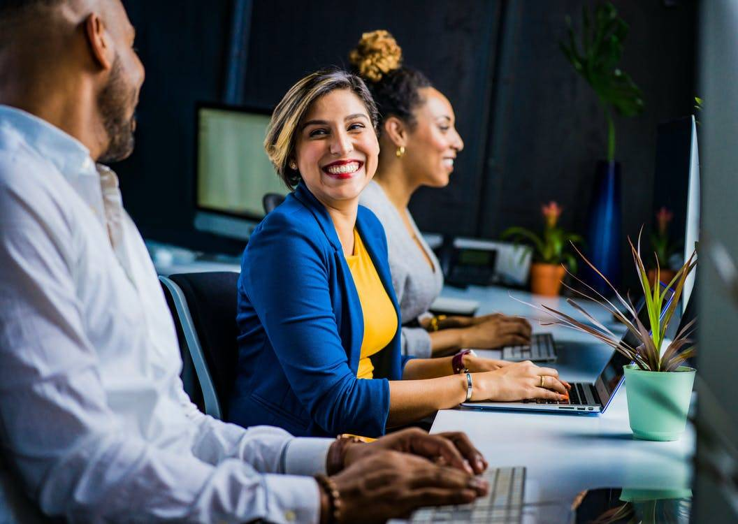 woman laughing with coworkers at work