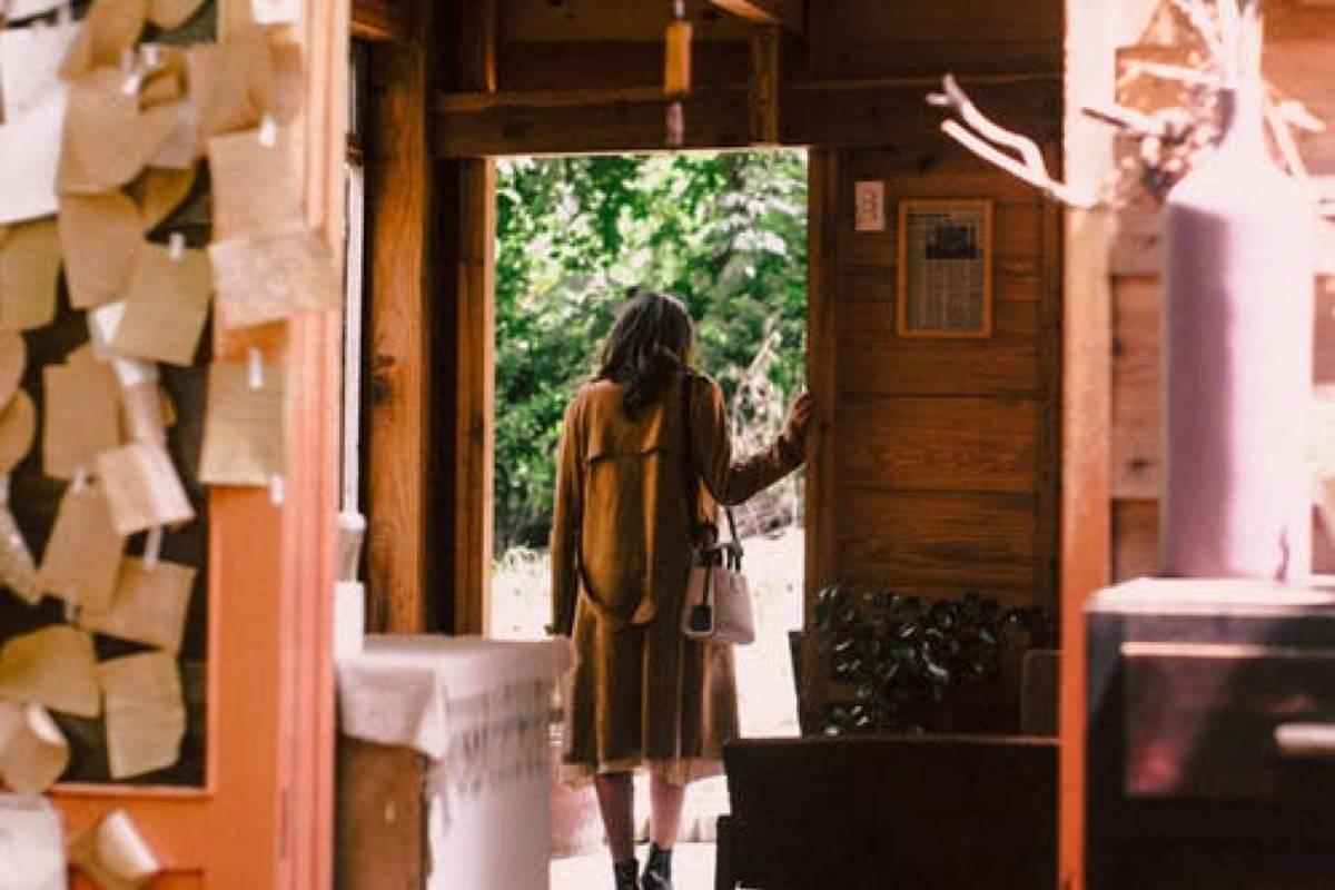 woman leaving house through front door