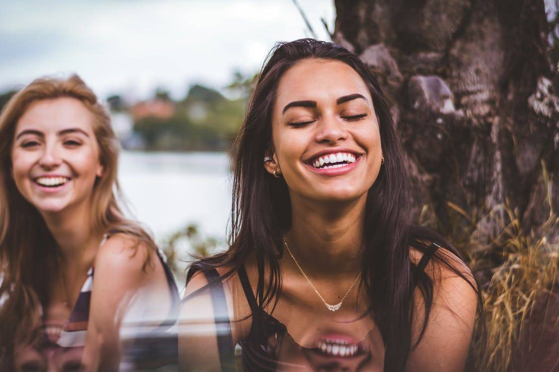 two women laughing outside together