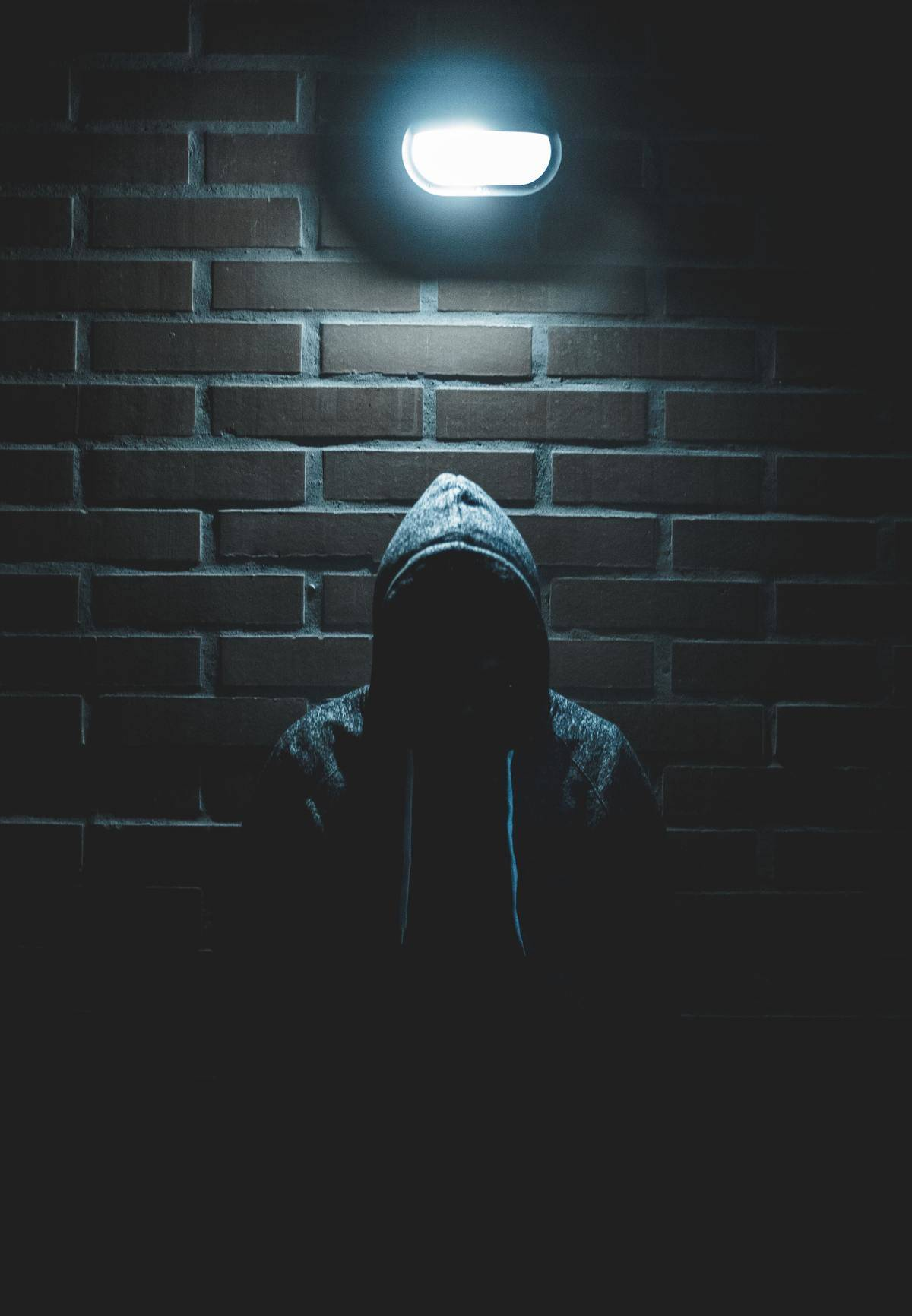 Man stands under streetlight wearing a hoodie with his face darkened by shadows