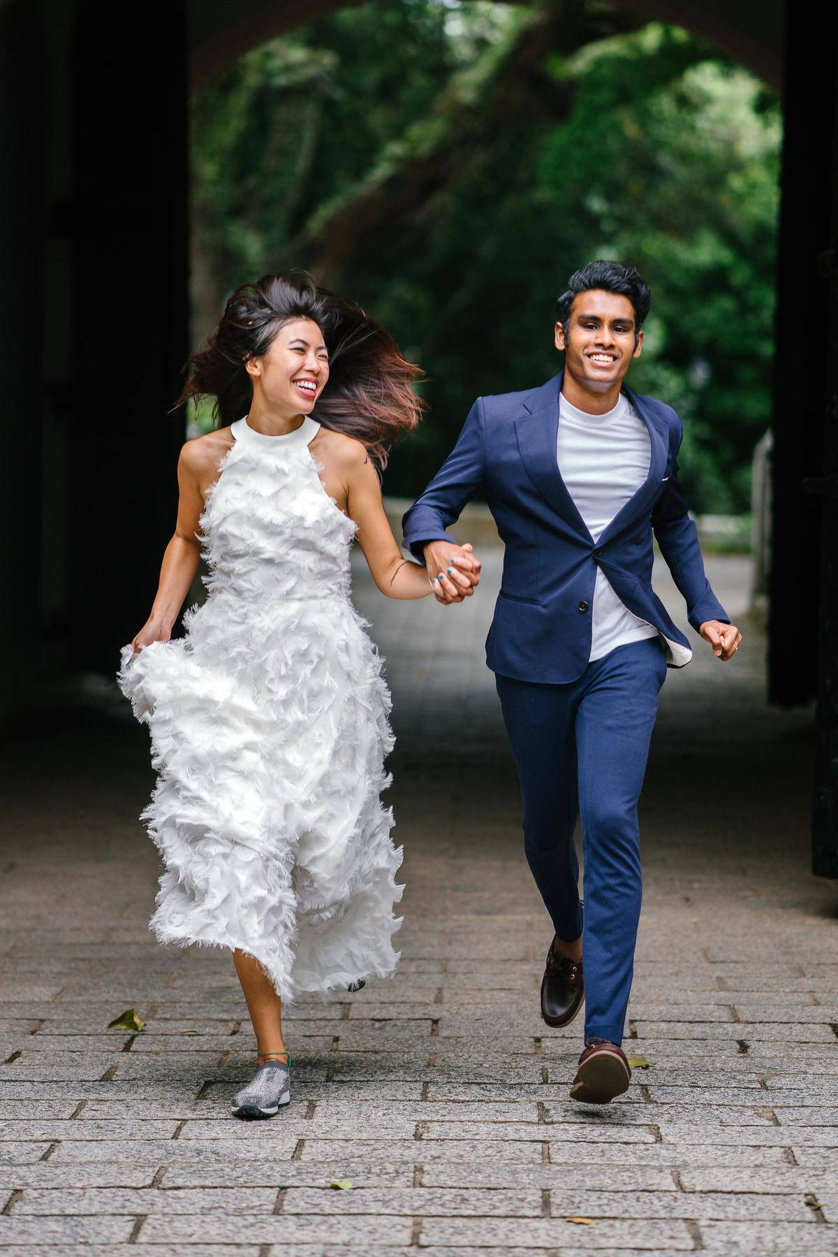 Bride and groom running and laughing together