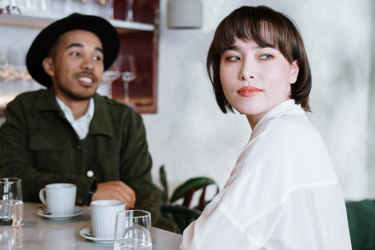 Couple at table with coffees, woman looks away