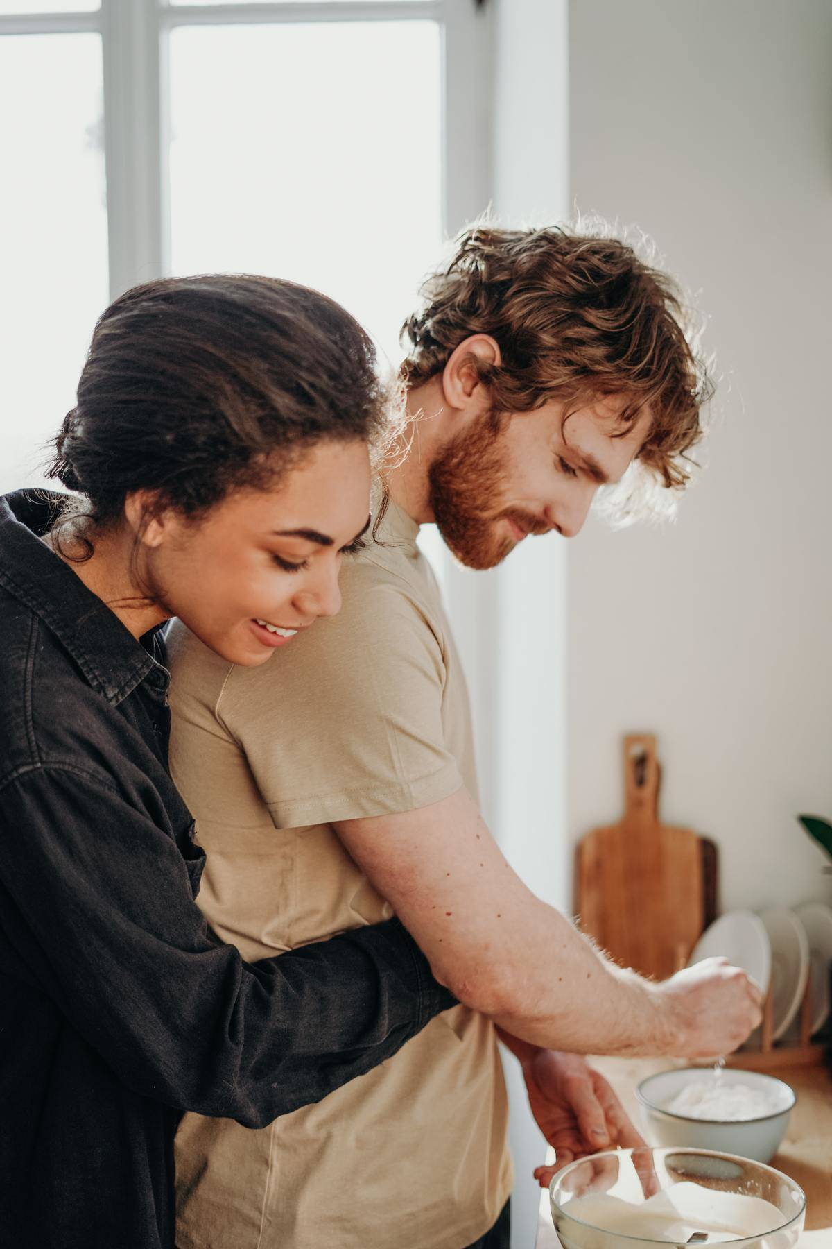 Young couple in kitchen, woman hugs man from behind