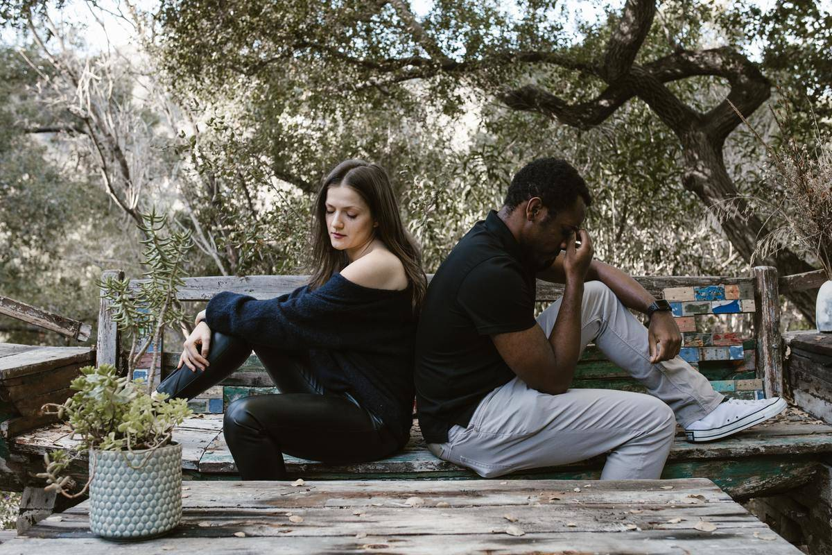 Couple sit outside in grass back to back