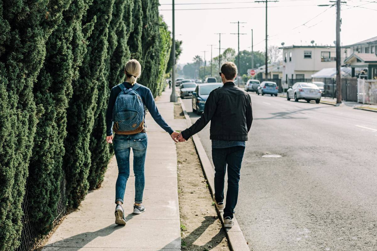 Couple holds hands walking away