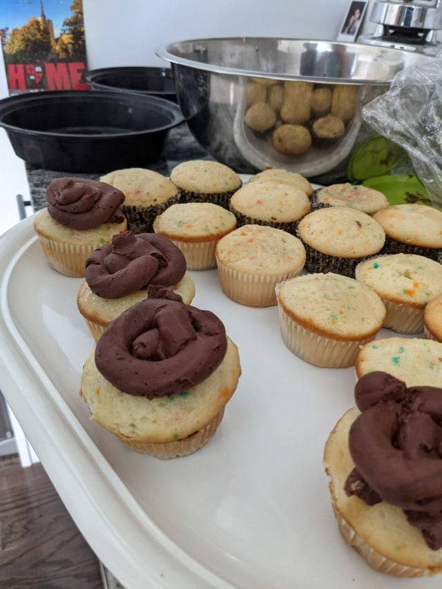 A wife's first attempt piping frosting on cupcakes that makes it look like a pile of poo
