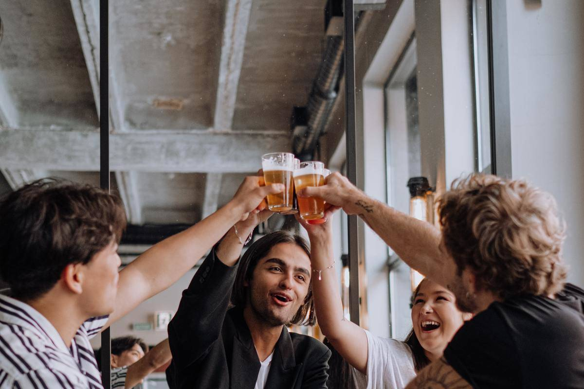 People cheers pints at table