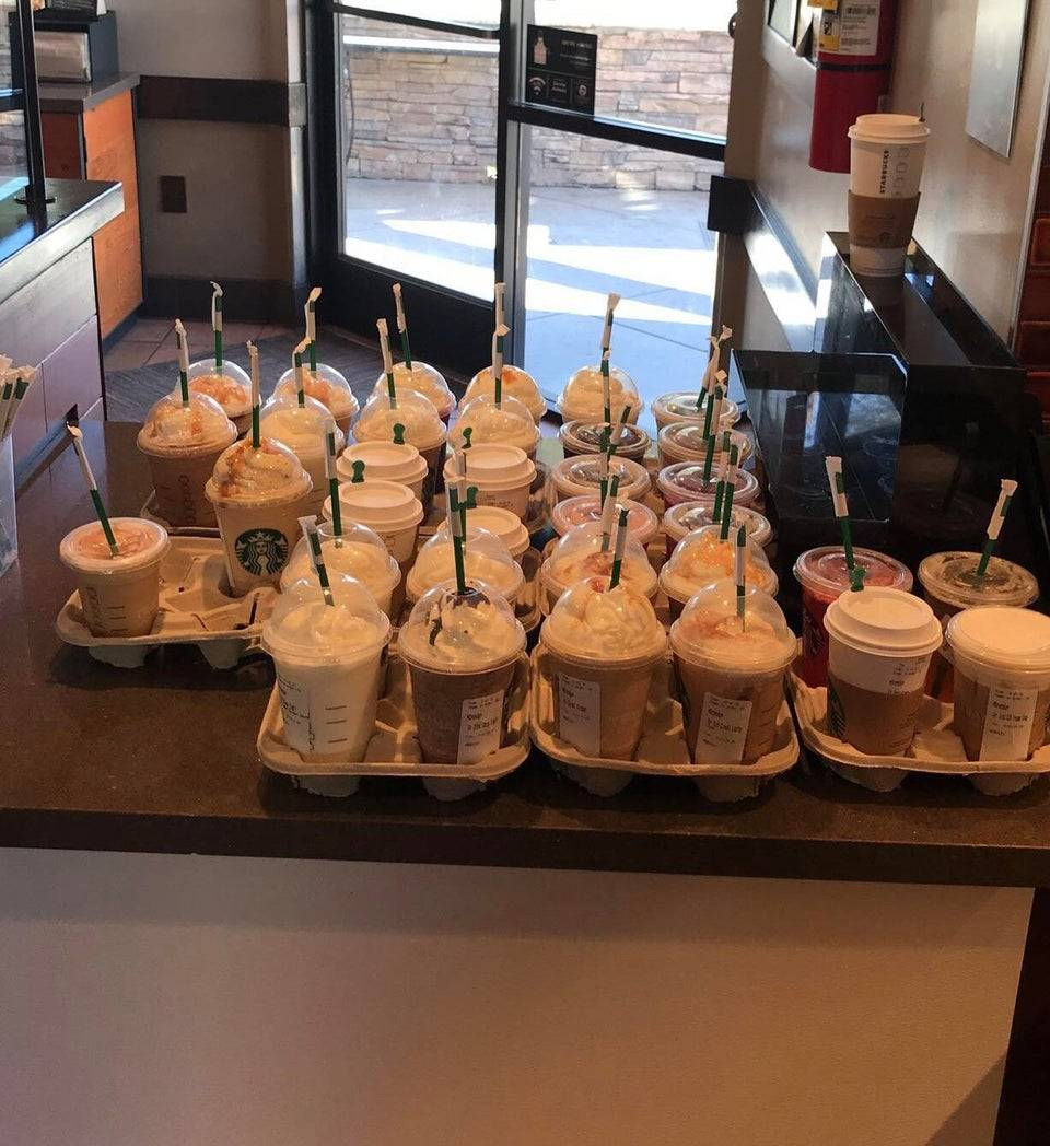 Close to 30 Starbucks drinks on the counter.