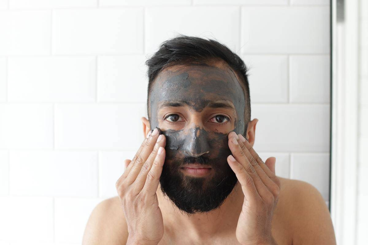 Man rubbing face mask on his face