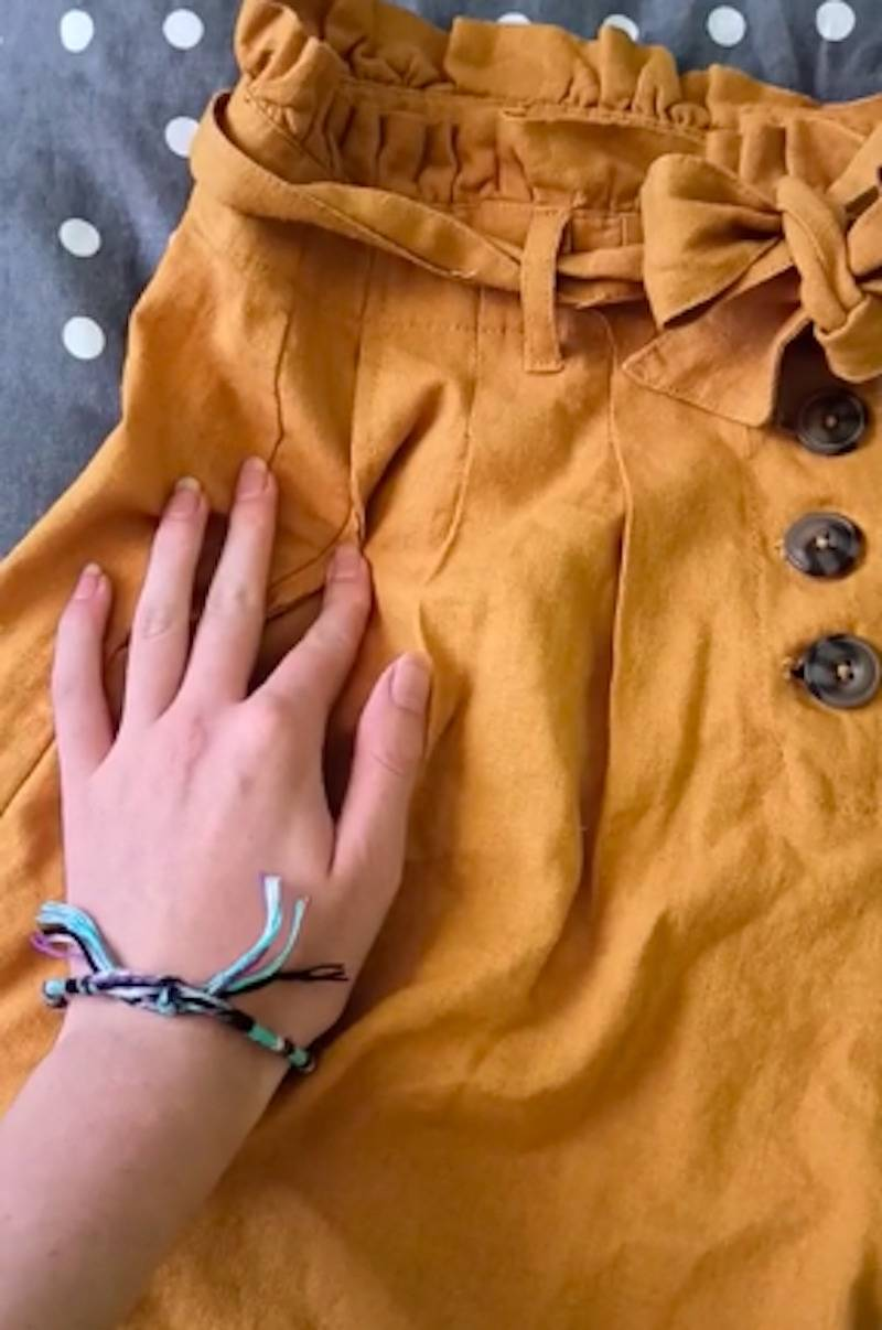 Woman shows how her new pair of orange shorts have four fake pockets.