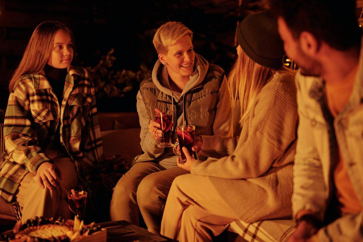 Group of friends sit outside at night socializing