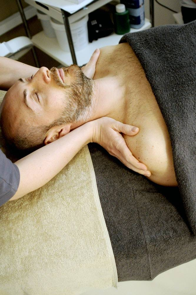 Man lying on table receiving massage