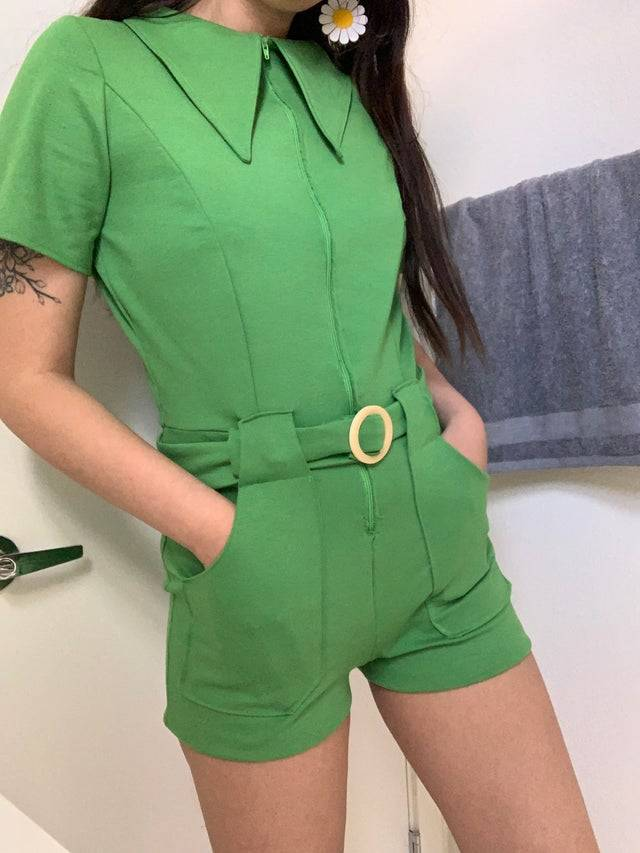 A photo of a woman wearing a green romper that she sewed together herself.