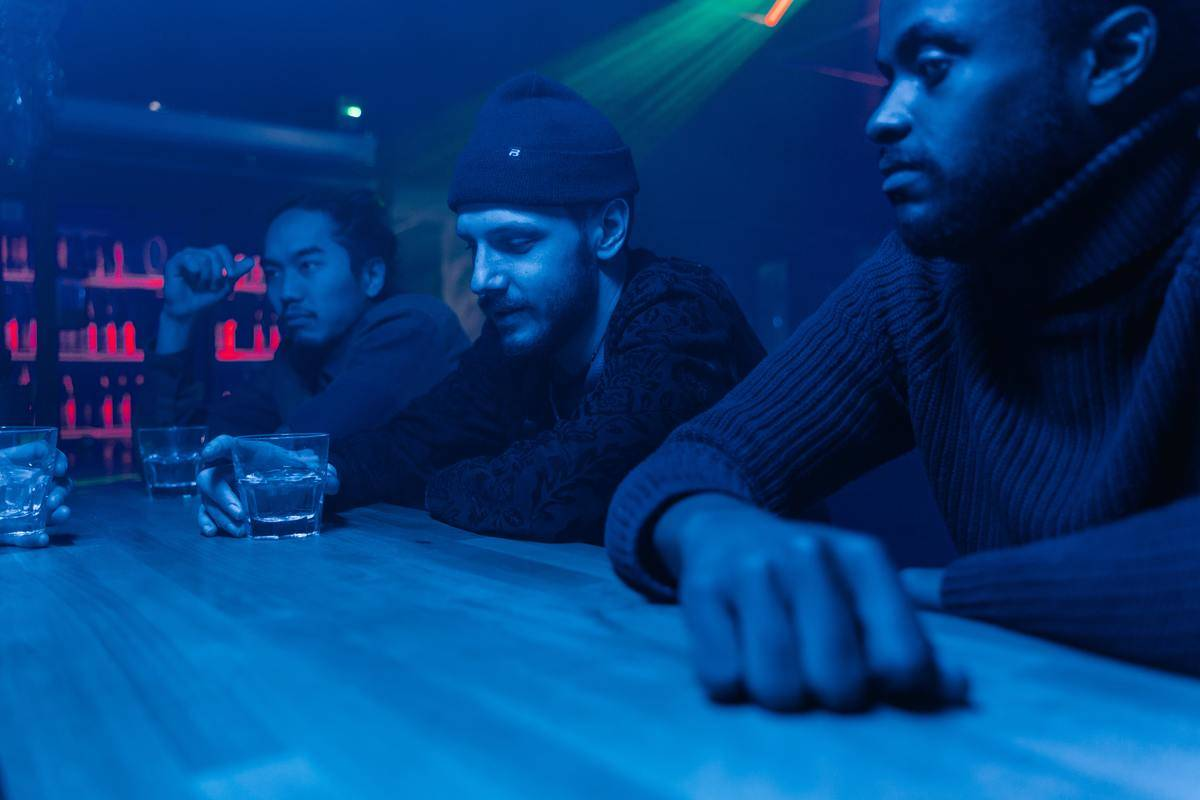 Guys at a bar in blue light