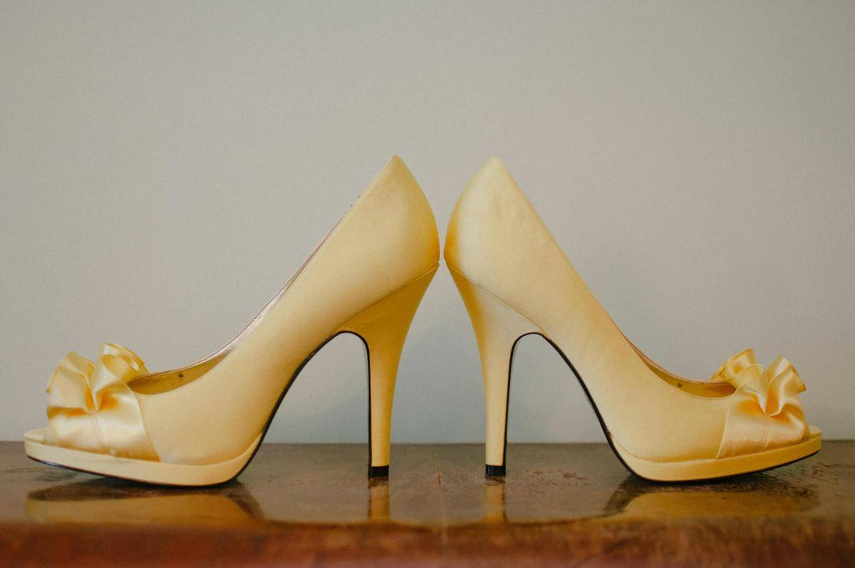 A pair of yellow high heels on a brown table