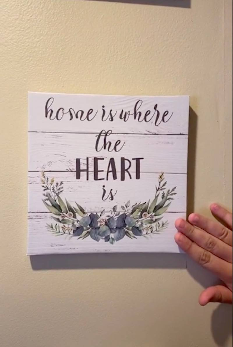 John points to one of his sister's home decor signs that say