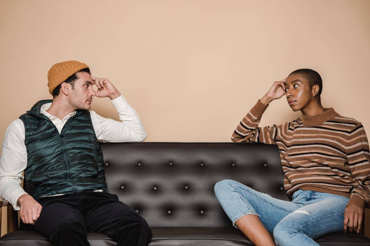 Man and woman sit and stare at each other on a leather couch, looking stern