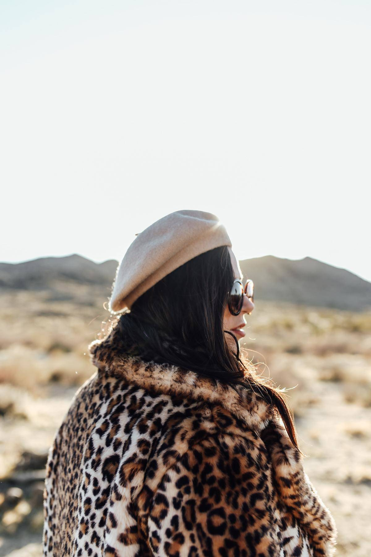 Woman looks off camera while wearing a leopard print coat.