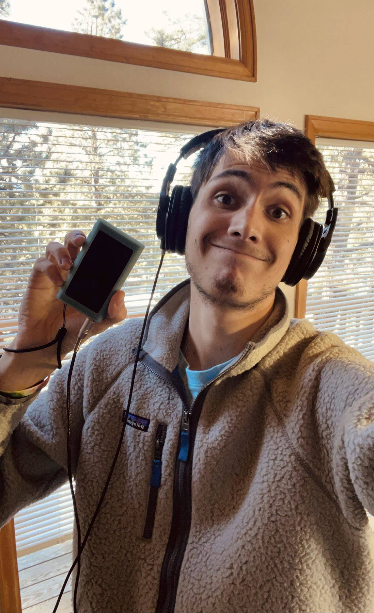 Man wearing headphones and holding an mp3 player