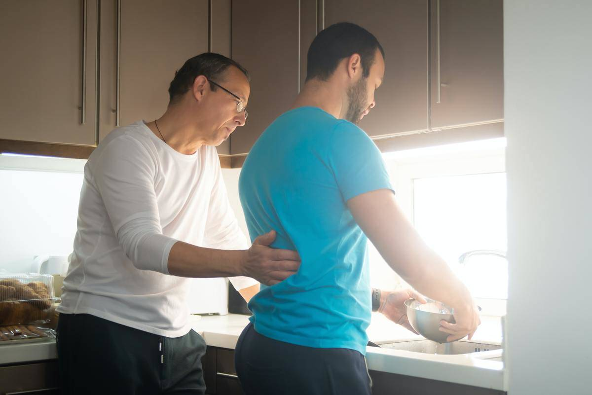 Couple older man and younger man in kitchen