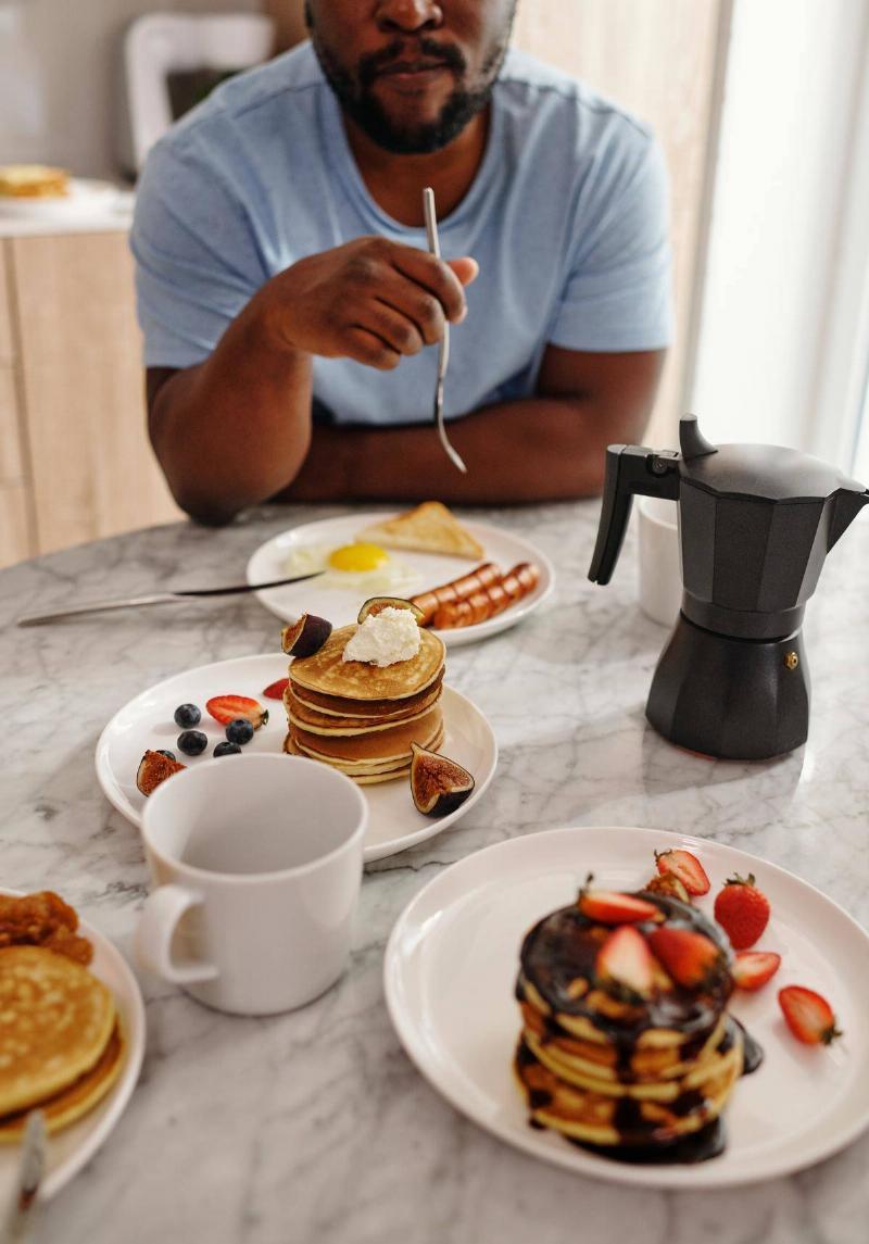 Man sits in front of prepared breakfast