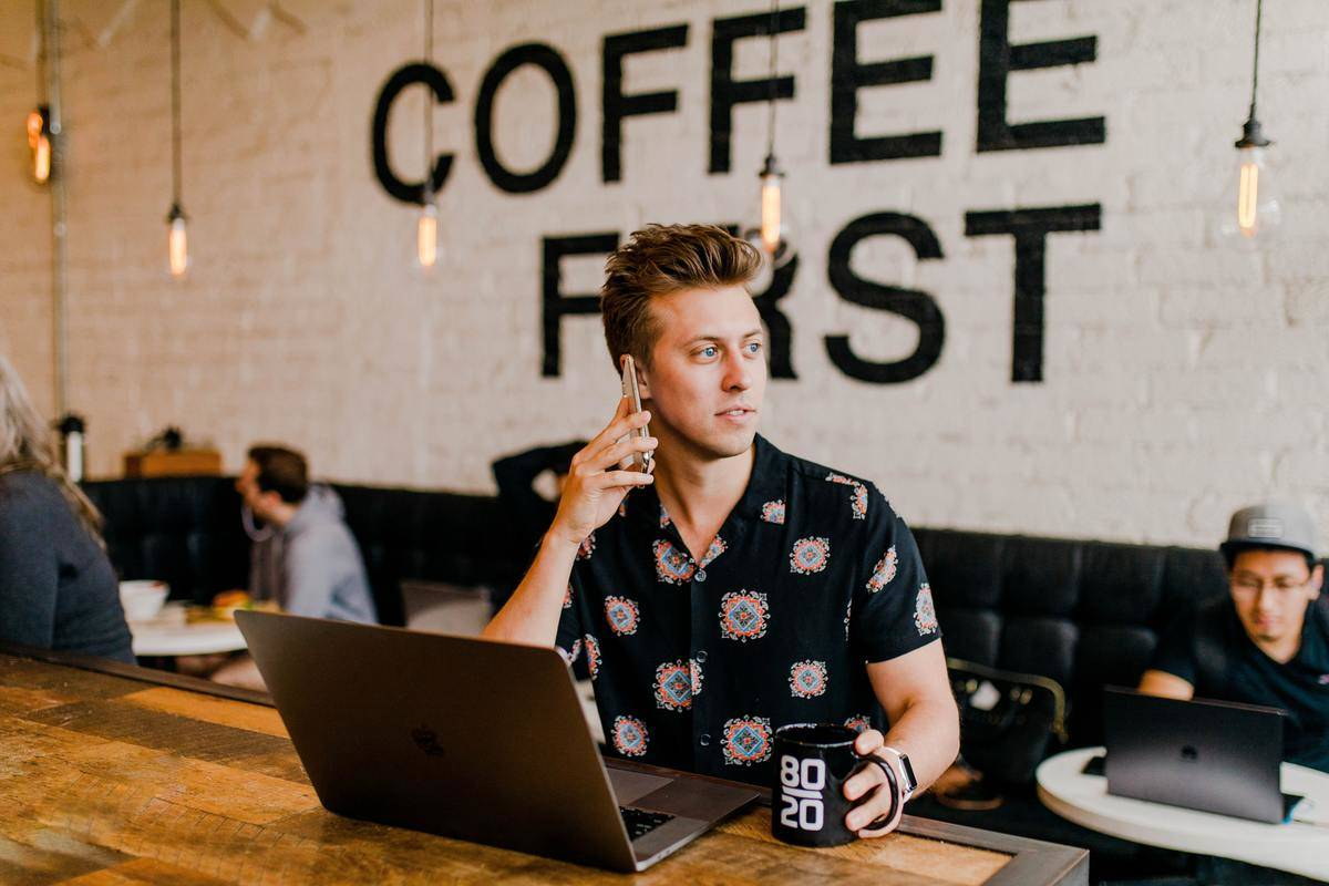 Man sits on cell phone at computer in coffee shop