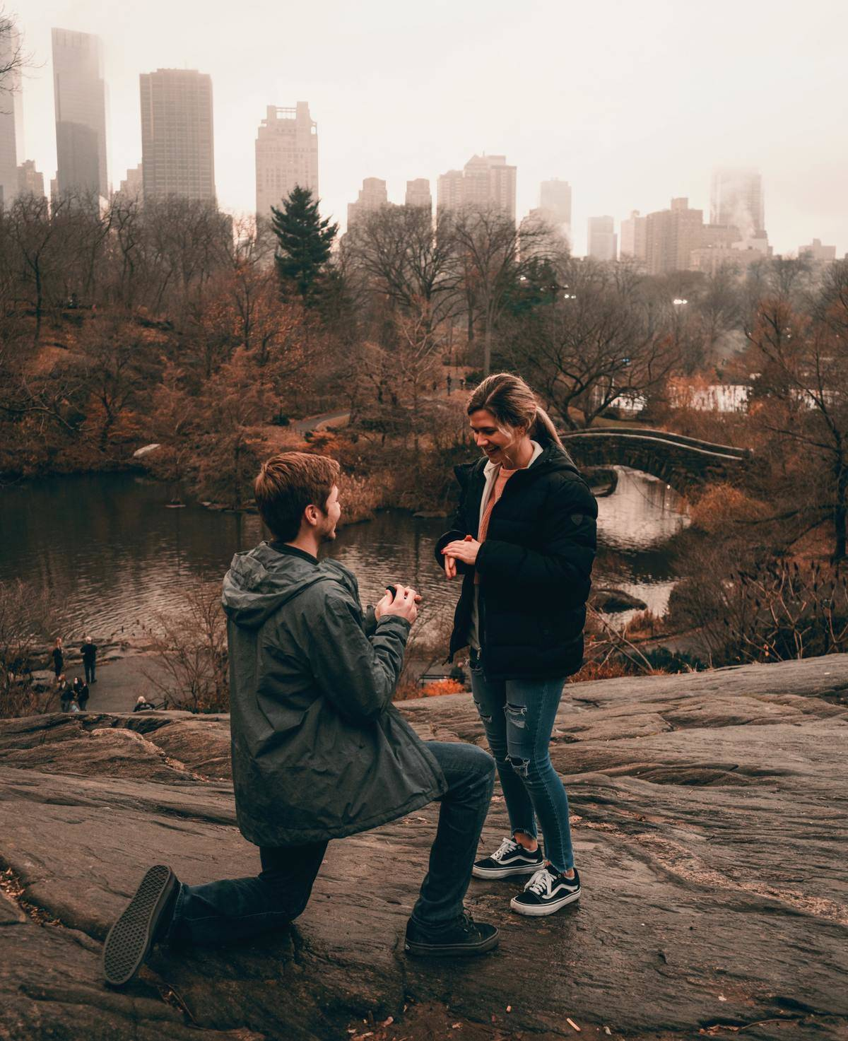 Man proposes to girlfriend in NYC's Central Park on an overcast autumn day.