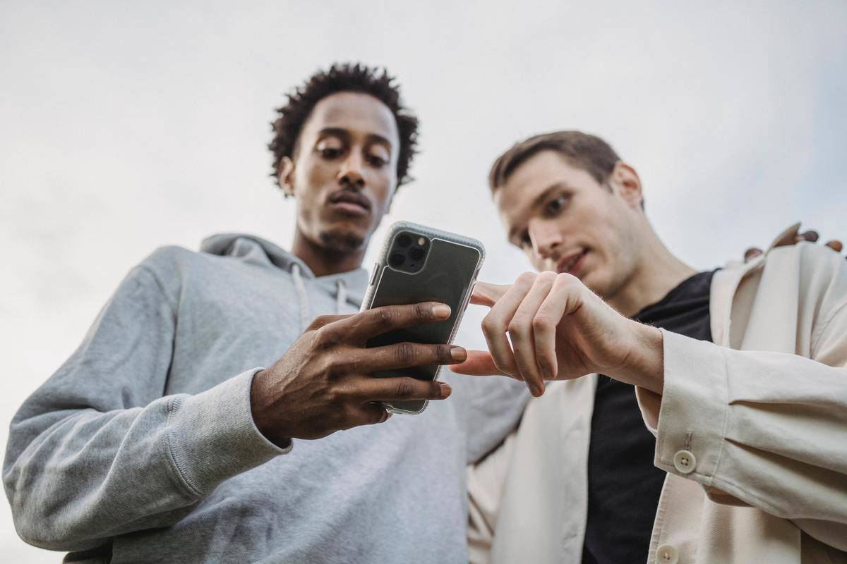 Two men look at cell phone screen