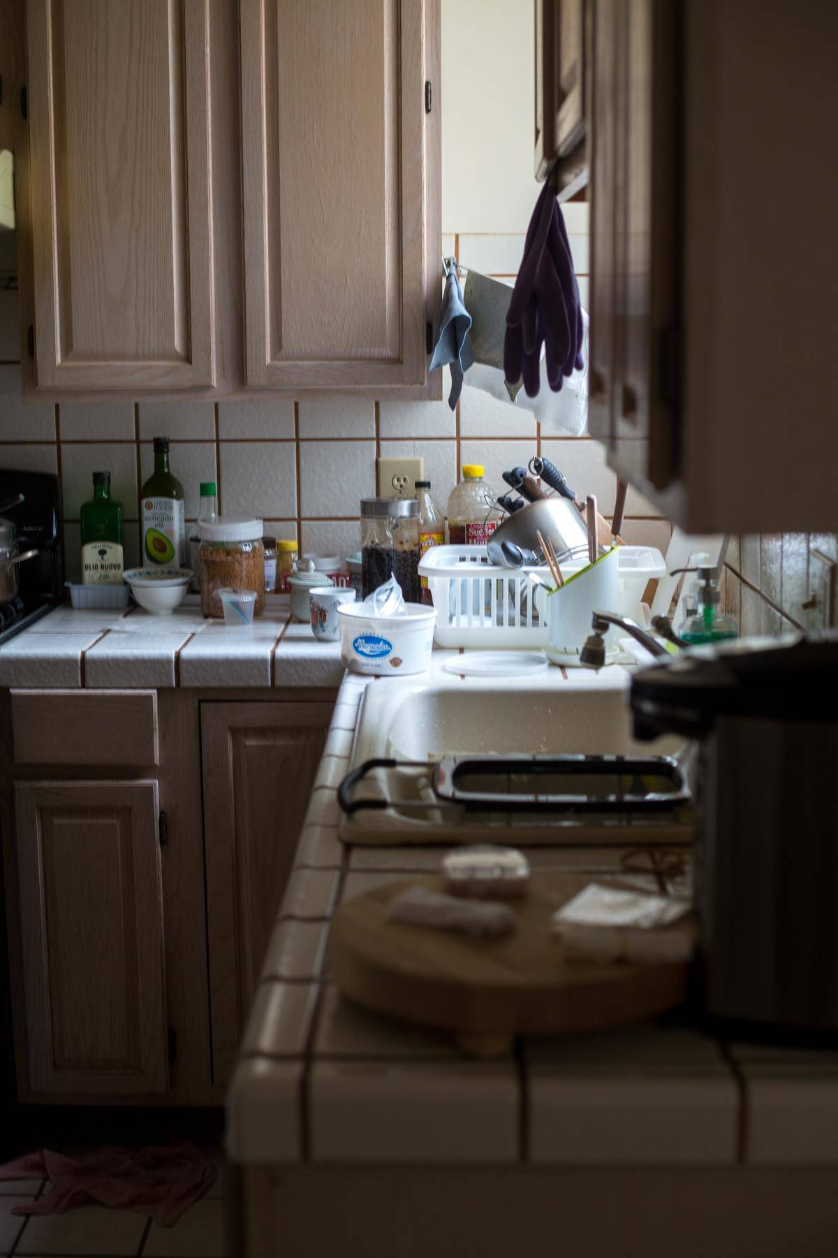 Messy kitchen with dishes falling out of sink