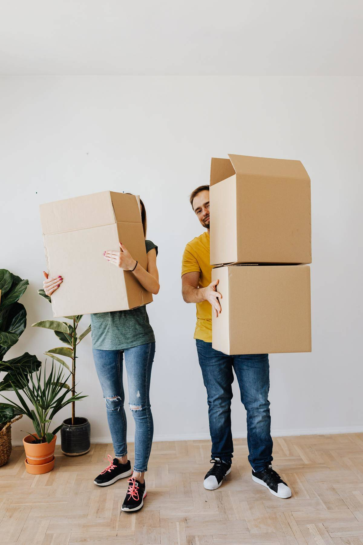 Man and woman look at the camera jokingly as they hold boxes and move into their new home