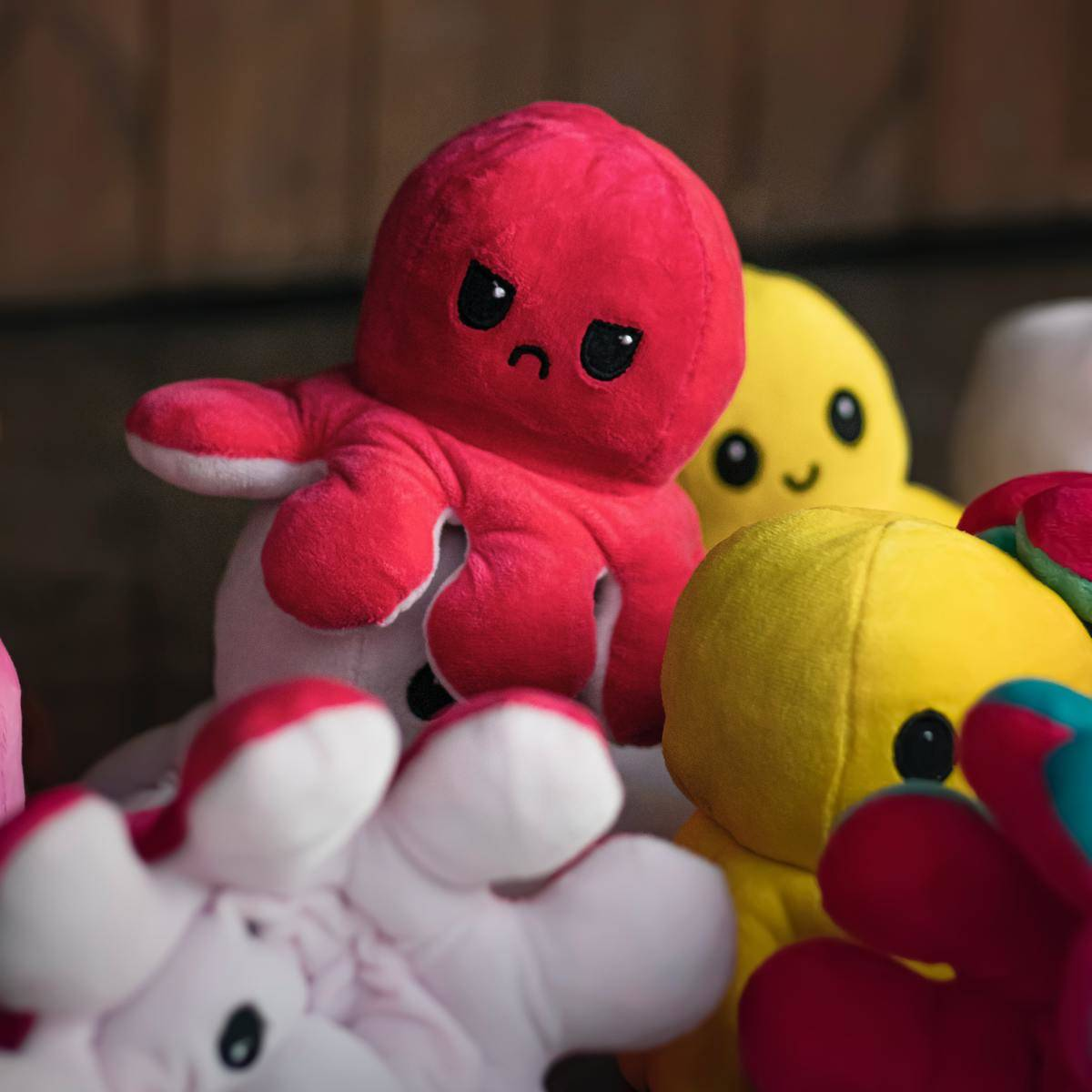 Octopus plushy toys, including a red one with an angry face