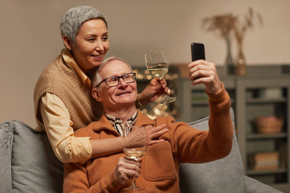 Senior couple on couch with glasses of wine talking selfie