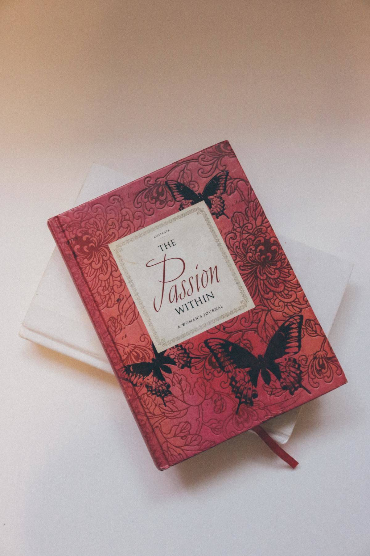 Red journal with black butterflies titled