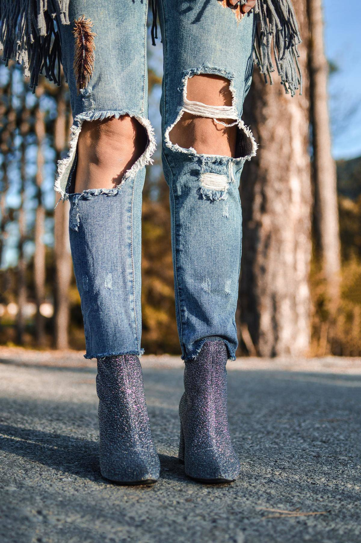 Close-up photo of a woman wearing jeans that have been ripped over the knees.