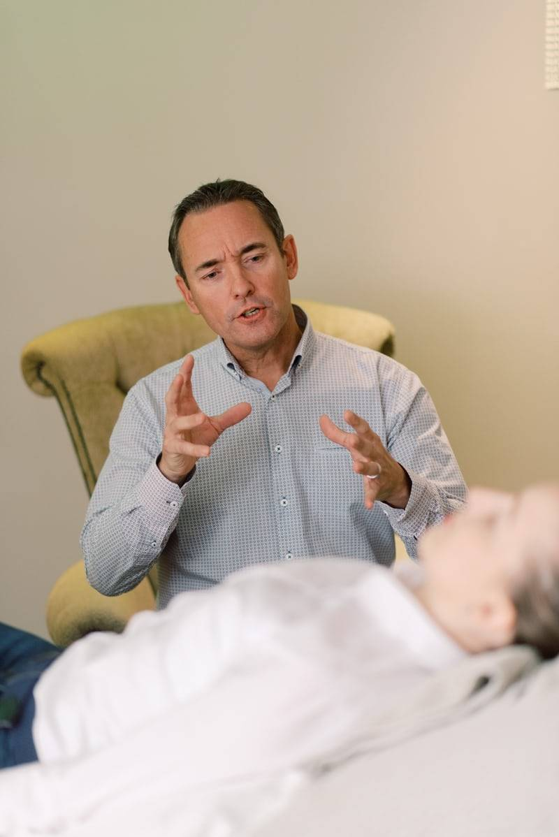 Therapist in a chair speaking to a patient who's laying down