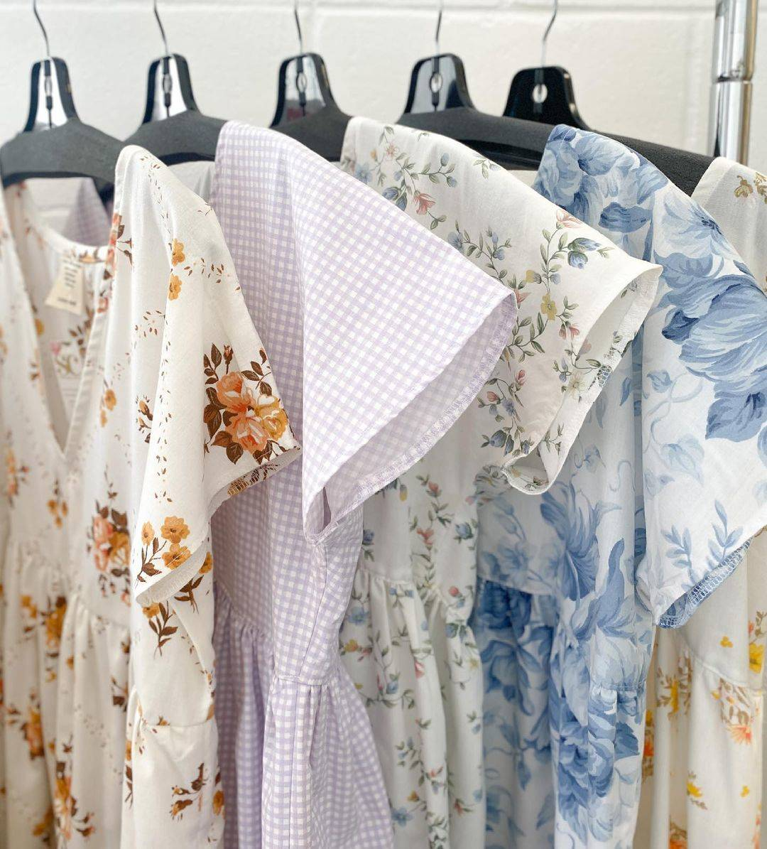 Several pastel-colored shift dresses hang on a clothing rack.