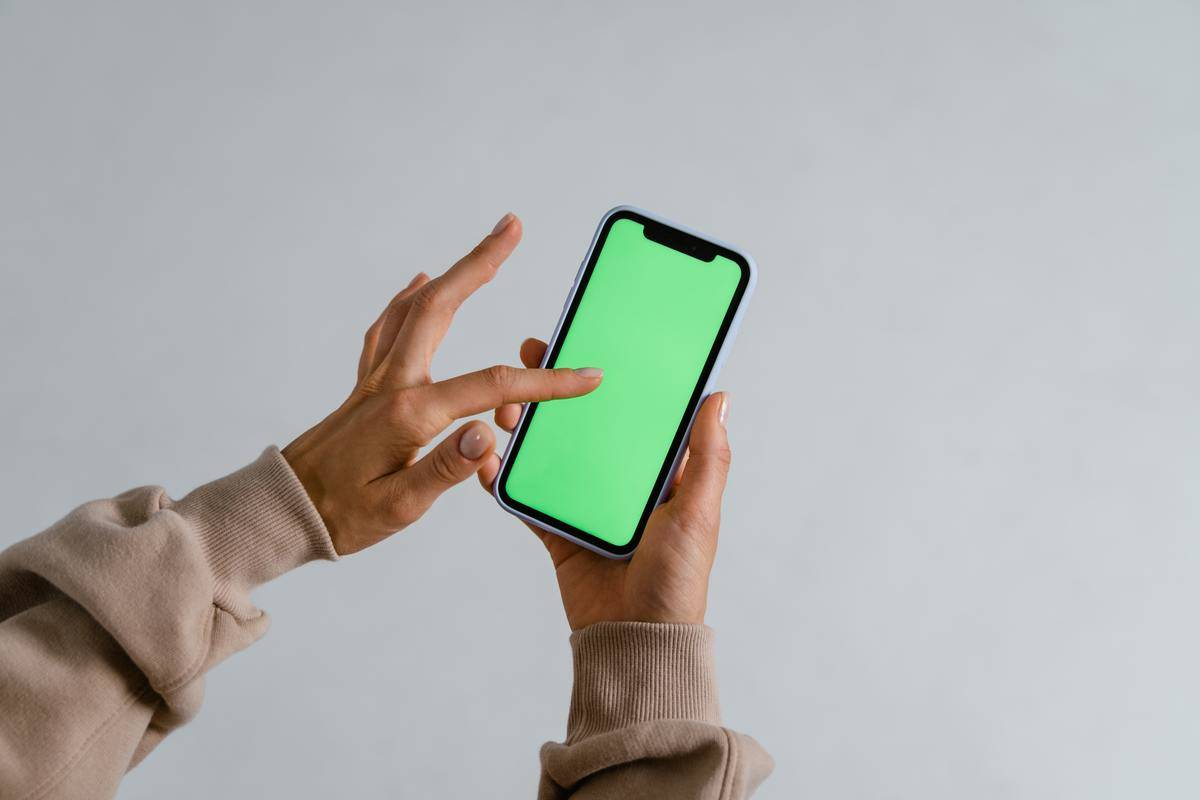 Hands swiping on phone which is displaying a green screen