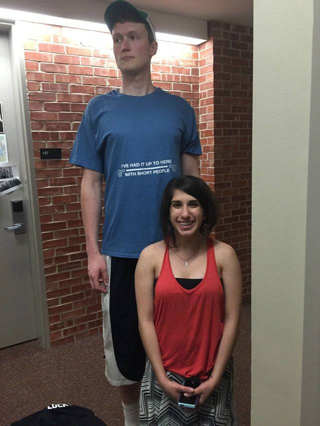 Short woman standing in front of a very tall man