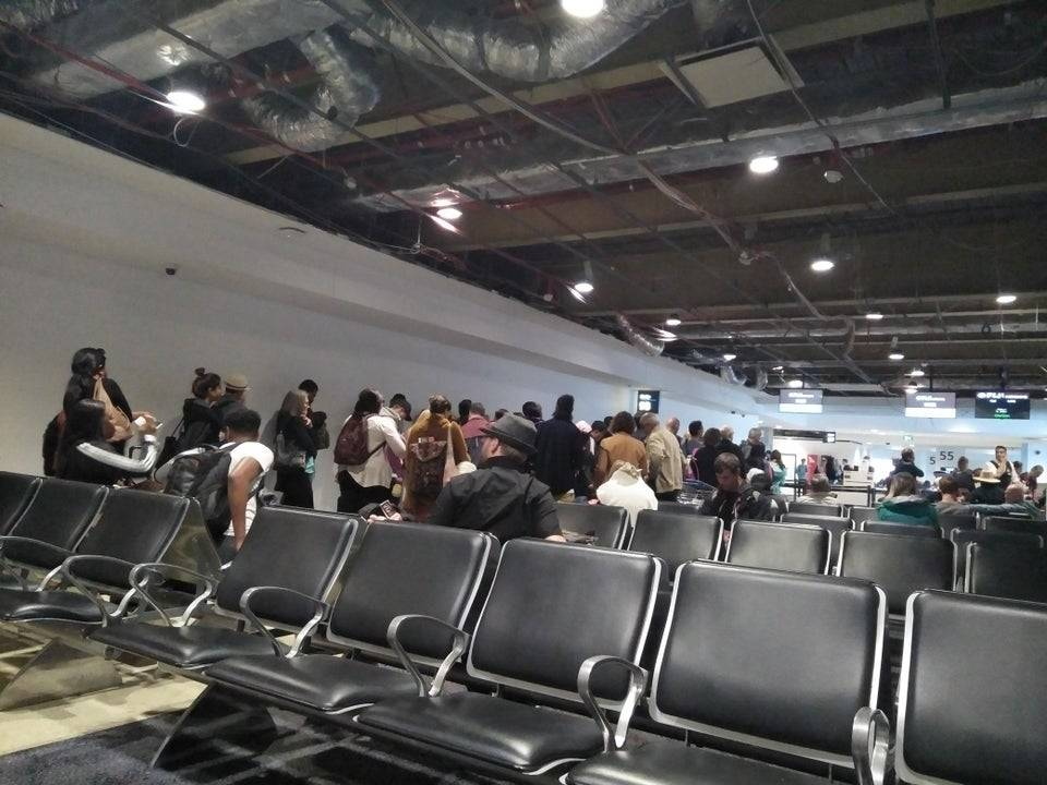 People lining up in airport terminal.