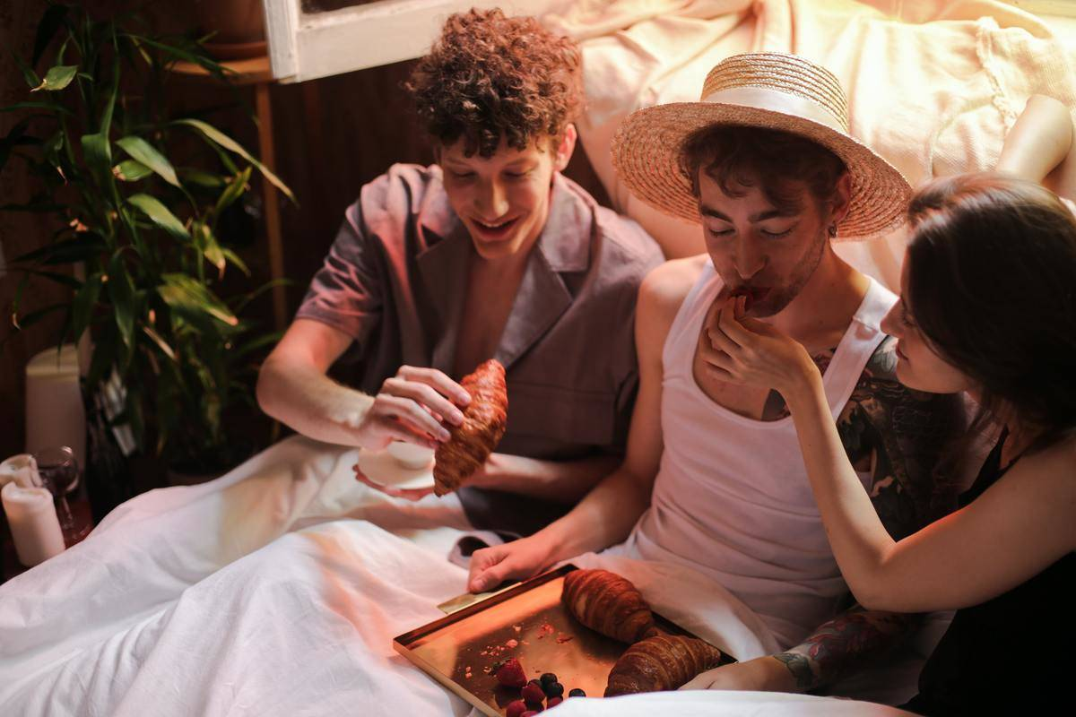Three people share breakfast in bed