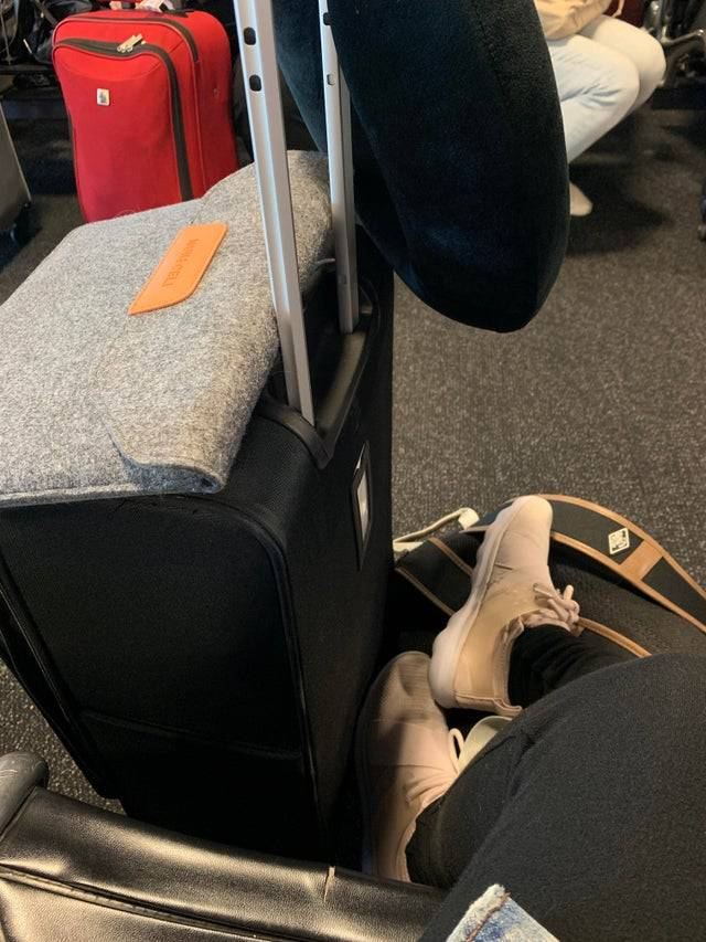 Person's legs beside luggage waiting in an airport.