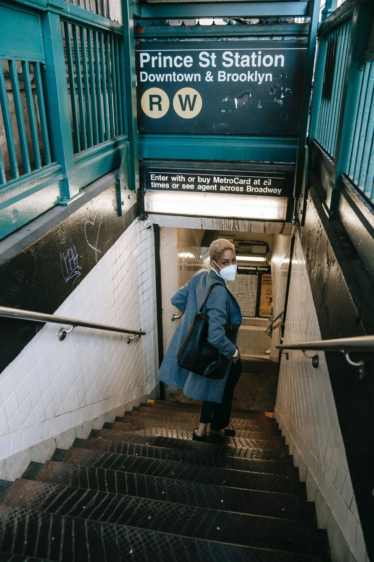 A woman walks down the stairs onto a subway platform and looks over her shoulder toward the camera